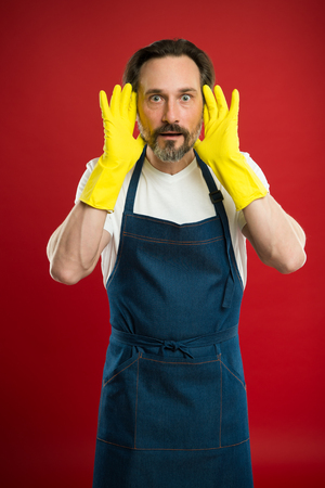 Man in apron with gloves cleaning agent. Cleaning day today. Bearded guy cleaning home. On guard of cleanliness and order. Cleaning service and household duty. Lot of work. Gardening concept.