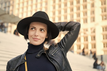 Beauty, look, makeup. Woman in black hat smile on stairs in paris, france, fashion. Fashion, accessory, style. Sensual woman with brunette hair, hairstyle Skincare youth visage