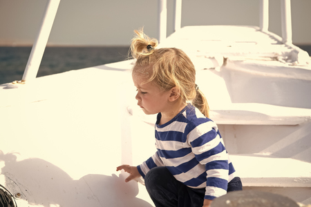 Boy in sailor shirt on blue sea. Summer vacation concept. Travel destination, cruise, travelling. Adventure, discovery, wanderlust. Child with blond hair on yacht on sunny day.