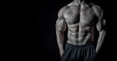 handsome bodybuilder man or muscular guy with athlete body, torso and chest training sport and posing in gym on black background, copy space