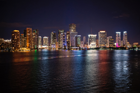 Miami city skyline panorama at night, usa. Skyscrapers illumination reflect on sea water in dusk. Architecture, structure, design. Building, construction, development. Wanderlust travel discovery