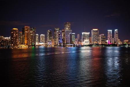 Panorama sur les toits de la ville de Miami la nuit, aux États-Unis. L'éclairage des gratte-ciel se reflète sur l'eau de mer au crépuscule. Architecture, structure, conception. Bâtiment, construction, développement. Découverte du voyage Wanderlust