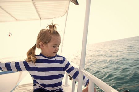 Travel destination, cruise, travelling. Adventure, discovery, wanderlust. Boy in sailor shirt sail in blue sea. Summer vacation concept. Child with blond hair on yacht on sunny day.