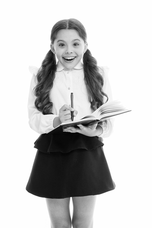 Write note to remember. Child school uniform smart kid happy make note. Child girl happy school uniform clothes holds book and write note. Girl surprised face make note about idea white background.