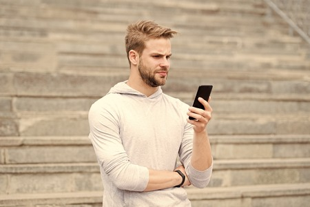 Man with beard walks with smartphone, urban background with stairs. Blogger use smartphone to stream video online. Man blogger using video conferencing on smartphone. Blogger concept.
