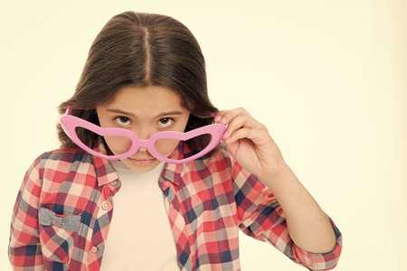 Girl cute, big heart shaped glasses isolated white background. Child girl looks wondered or surprised. Are you serious. Kid peeking out of glasses, copy space. Child can not believe her eyes. Stock fotó