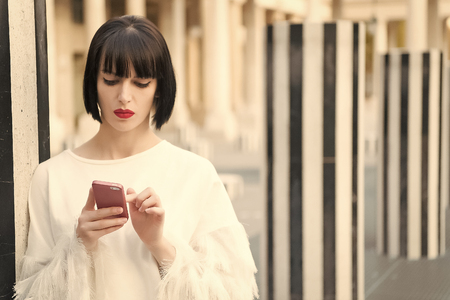 New technology for modern life. Woman with red lips use on smartphone in paris, france. Woman with brunette hair hold mobile phone. Beauty girl with sexy look. Fashion model with mobile device. Stock fotó
