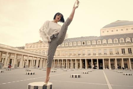Jeune femme élégante en pantalon avec fente sur rue à Paris, France. concept de dace et de yoga. pose de danse Banque d'images