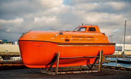 Reykjavik, Iceland - October 14, 2017: maritime safety and survival training centre boat on sea shore. Orange boat or lifeboat on cloudy sky. Safety or search and rescue. Transport and transportation.