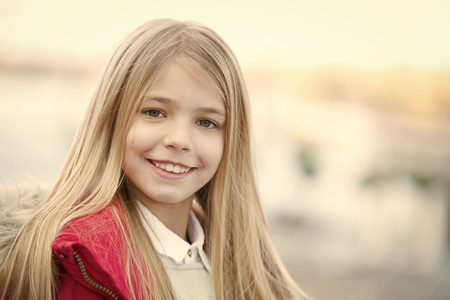 Girl with blond long hair on autumn day outdoor. Child smile on blurred environment. Kid fashion and style. Happy childhood concept. Beauty, look, hairstyle.