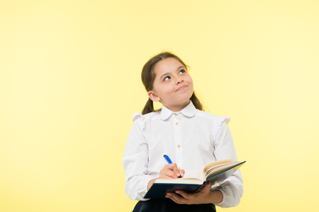 Child school uniform kid doing homework. Child girl school uniform clothes hold book and pen. Girl cute write down idea notes. Notes to remember. Write essay or notes. Personal schedule. Making notes. Stock fotó