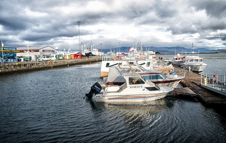 Reykjavik, Iceland - October 13, 2017: motor boats at sea pier in small village. Yachts at sea coast on cloudy sky. Water transport and travel by boat. Vacation or wanderlust and travelling.