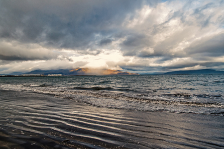 Sea waves on sandy beach in reykjavik, iceland. Seascape with grey water on cloudy sky. Power of nature. Wanderlust or travelling and vacation.