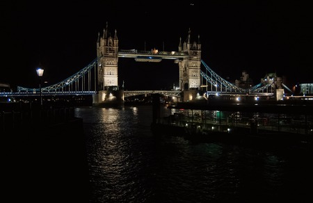 Tower bridge with night illumination in London, United Kingdom. Bridge over Thames river with dark water with nice architecture. Structure and design. Wanderlust and vacation concept.