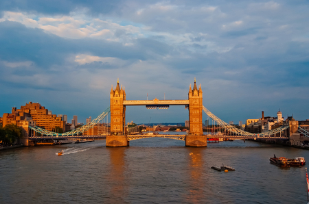 Tower bridge in London, United Kingdom. Bridge over Thames river on cloudy sky. Buildings on river banks with nice architecture. Structure and design. Wanderlust and vacation concept.