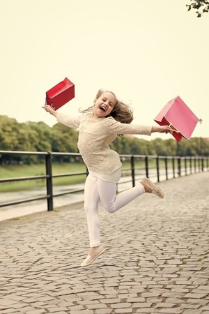 shopping concept. Pretty little girl running on the street with the pink shopping bags Stock Photo
