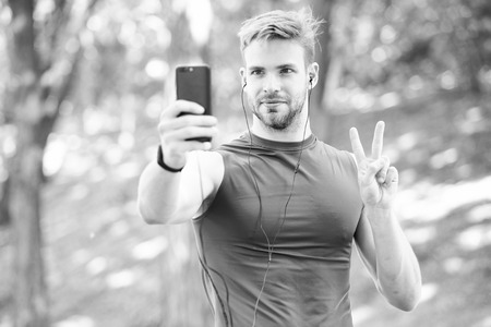 Man athlete concentrated face take smartphone photo nature background. Sportsman take photo winner sport competition. Athlete fitness tracker and smartphone. Capture victory moment. Victory gesture.