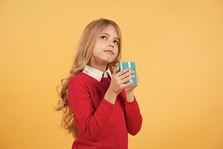 Child with thinking face hold blue cup on orange background. Tea or coffee break. Thirst, dehydration concept. Health and healthy drink. Girl with long blond hair in red sweater with mug, copy space