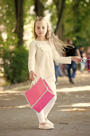 shopping concept. Pretty little girl walking with the pink shopping bags