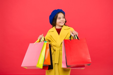Obsessed with shopping. Girl cute kid hold shopping bags. Get discount shopping on birthday holiday. Nice purchase. Fashionista enjoy shopping. Customer satisfaction. Prime time buy spring clothing. Stock Photo