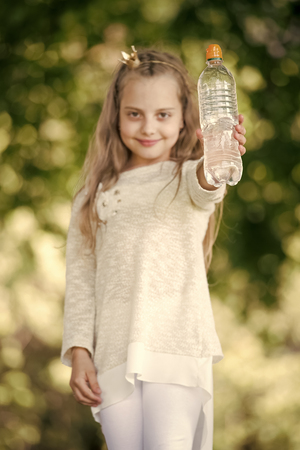 Lovely happy little girl drinking water at summer day 写真素材