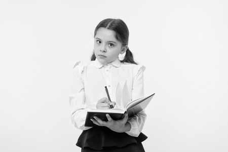 Girl cute schoolgirl in uniform hold book with information yellow background. Pupil get information from book. Child wear school uniform prepare for lesson information. Noticing information.