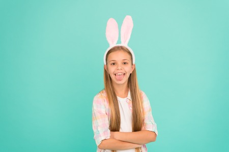Fashion accessory for easter costume party. Looking pretty in easter bunny attire. Cute little girl wearing bunny ears headband. Small girl child showing tongue in easter bunny style. Funny cutie. Reklamní fotografie