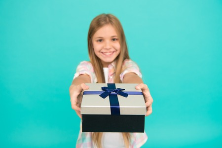 This is for you. Little shopaholic giving present wrapped in box. Small child with gift box tied with ribbon bow. Cute shopper enjoy doing a little shopping. Small girl after shopping for gift.