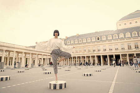 Beauty girl stand in yoga pose in paris, france. Beauty model pose in high heel shoes on column. Reklamní fotografie
