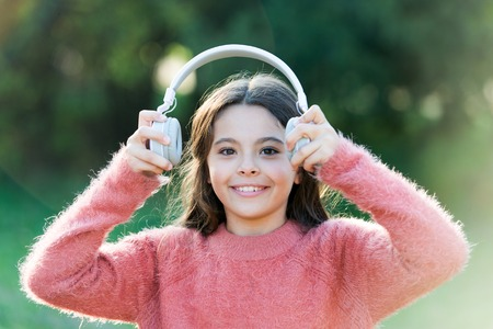 All she wants to hear is music. Adorable little girl outdoor. Little girl child wearing headphones. Happy child enjoy listening to music on the go. Having incredible sound for all her entertainment.