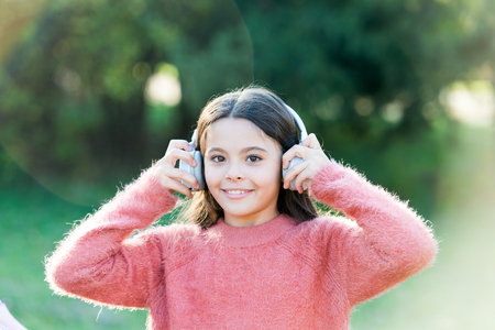 Keeping her connected to her entertainment. Adorable little girl outdoor. All she wants to hear is music. Little girl child wearing headphones. Happy child enjoy listening to music on the go.
