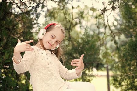 Cute little girl enjoying music using headphones at summer day