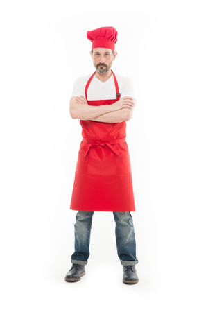 Known for his cooking. Bearded mature man in chef hat and apron. Senior cook with beard and moustache wearing bib apron. Mature chief cook in red cooking apron. Home cooking.