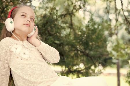pretty little girl listening and enjoying music using headphones at summer day Reklamní fotografie