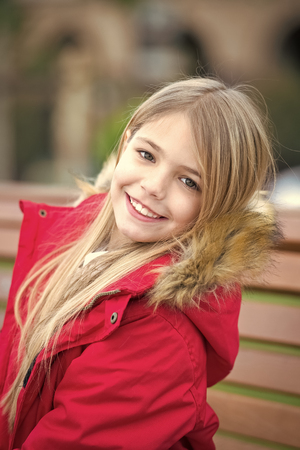 Happy childhood concept. Girl in red coat sit on bench in park. Child with blond long hair smile outdoor. Kid enjoy autumn day. Leisure, relaxation, lifestyle.