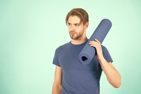 Sportsman hold yoga mat. Fashion athlete in blue tshirt. Bearded man with stylish hair. Gym equipment for training and workout. Sport yoga and pilates activity, copy space.