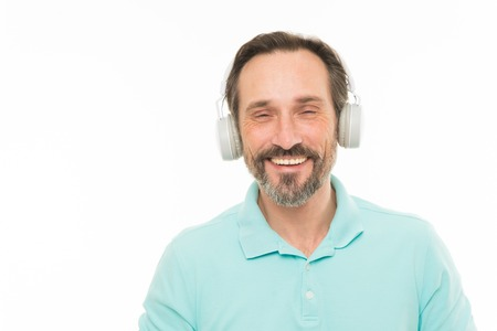 Live life loud. Mature man in stereo headphones. Happy bearded man listening to music via earphones. Elderly man enjoying music playing in headset. Feeling the rhythm of the music, copy space. Reklamní fotografie