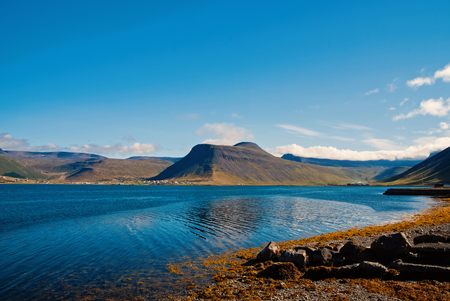 Summer vacation in isafjordur, iceland. Hilly coastline on sunny blue sky. Mountain landscape seen from sea. Discover wild nature on scandinavian island. Wanderlust and travelling concept. Reklamní fotografie