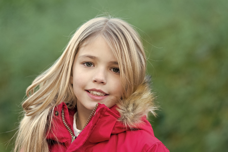 Beauty, nature, growth. Child in red coat enjoy idyllic autumn day. Innocence, purity and youth. Happy childhood concept. Girl with blond long hair smile on natural environment. Reklamní fotografie