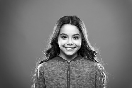 Girl cute child happy smiling face. Child long hair happy smiling. Happy childhood concept. What science has to say about genuine and fake smiles. What is difference between phony and sincere smile. Stock Photo