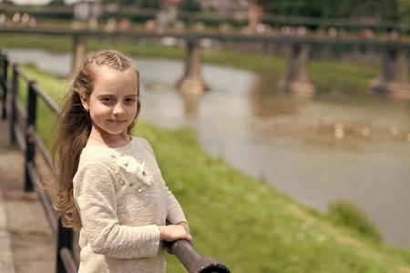 Girl child tourist enjoy sightseeing while walks. Kid girl with long hair walks near riverside, river on background. Girl or schoolgirl on vacation enjoy travelling and sightseeing. Vacation concept.