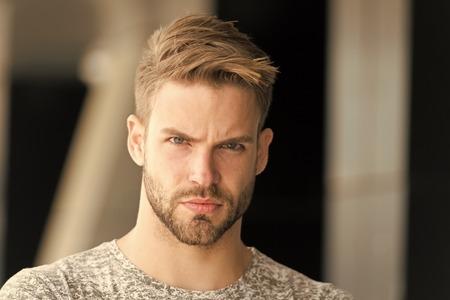 Concept métrosexuel. L'homme à la barbe non rasé a l'air beau et cool. Beau dans le style. Guy barbu attrayant se soucie de l'apparence. Soies de l'homme sérieux visage strict, fond noir se bouchent. Banque d'images