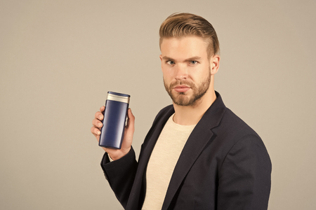 Manager with shampoo or gel bottle in hand. Bearded man with stylish hair or haircut. Cosmetic for spa bath or shower. Hair care and beard grooming. Mens beauty and health. Фото со стока