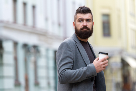 One more sip of coffee. City lifestyle. Businessman well groomed appearance enjoy coffee break out of business center urban background. Relax and recharge. Man bearded hipster drink coffee paper cup.