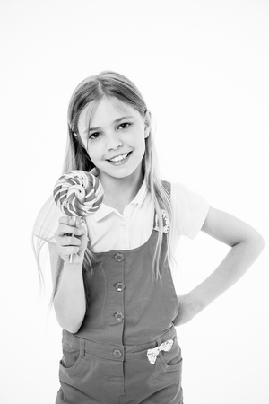 Little girl with lollipop. Little girl hold lollipop candy on stick. Happy childhood years. She has a sweet tooth. Food that reminds you of your childhood.