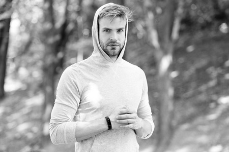 Jogging his way to good health. Sportsman training with pedometer gadget. Athlete with fitness tracker or pedometer ready for workout. Man athlete strict face with sport equipment nature background.