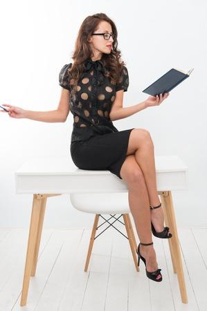Femme d'affaires lisant un livre alors qu'elle était assise sur une table de bureau. Banque d'images