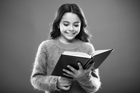 Useful information for her. Girl hold book read story over orange background. Child enjoy reading book. Book store concept. Wonderful free childrens books available to read. Childrens literature. Banco de Imagens - 122263944