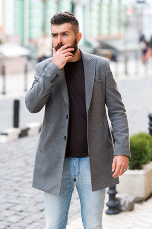 Businessman catching taxi while standing outdoors urban background. Man bearded hipster casual style waiting for taxi. Guy at street city center. Looking for transportation. Bus stop. Taxi please. Stock Photo