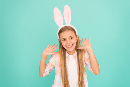 Easter activities. Cute bunny. Holiday bunny girl posing with cute long ears. Child smiling play bunny role. Happy childhood. Traditions for kids to help get in easter spirit. Bunny ears accessory. Imagens